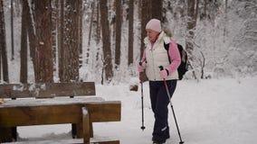 Seitenansicht der aktiven Frau den Nordic tuend, der draußen mit Skipfosten in der Winternatur geht Dame im Ruhestand, die Pickni stock video footage