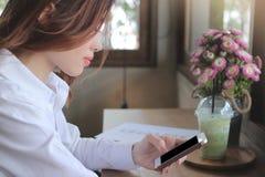 Seitenansicht der attraktiven jungen asiatischen Geschäftsfrau, die intelligentes Mobiltelefon in ihren Händen im Kaffeecafé scha Lizenzfreie Stockfotografie