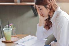 Seitenansicht der attraktiven jungen asiatischen Geschäftsfrau, die Schreibarbeit oder Diagramme auf dem Schreibtisch schaut Lizenzfreie Stockfotos