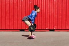 Seitenansicht der Eignungsfrau Übung mit Gewichten tuend Stockfotografie