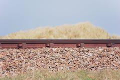 Seitenansicht der Eisenbahnlinie zwischen Sanddünegräsern Lizenzfreies Stockbild