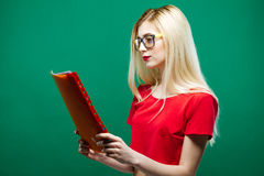 Seitenansicht der ernsten Studentin in den Brillen und in der roten kurzen Spitzenlesung etwas auf grünem Hintergrund im Studio Stockbild