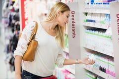 Seitenansicht der Frau desodorierendes Mittel wählend Lizenzfreies Stockfoto