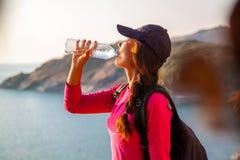 Seitenansicht der Frau mit Rucksack und einer Flasche Wasser Meer beim Sitzen betrachtend auf Hügel gegen Himmel lizenzfreie stockfotos