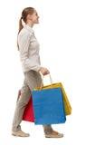 Seitenansicht der gehenden Frau mit Einkaufstaschen Stockbilder