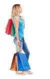 Seitenansicht der gehenden Frau mit Einkaufstaschen Stockbild
