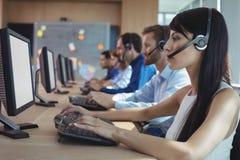 Seitenansicht der Geschäftsfrau schreibend auf Tastatur in Call-Center stockfotografie