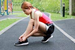 Seitenansicht der gesunden Asiatin Spitzee auf Laufschuhen auf der Straße binden Eignung und Training Wellness-Konzept stockfotografie