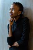 Seitenansicht der glücklichen lächelnden jungen schwarzen Frau, die weg mit der Hand unter dem Kinn, grauer Hintergrund schaut Stockfoto