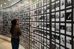 Seitenansicht der jungen Frau steht in einer Kunstgalerie vor Fotografie oder im Bild, das auf einer weißen Wand angezeigt wird Stockfotografie