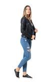 Seitenansicht der jungen Schönheit in zerrissenen Jeans und schwarzen in der Jacke, die oben schaut Stockfotos