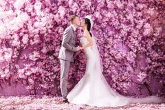 Seitenansicht der küssenden weißen Stellung der Hochzeitspaare gegen die Wand bedeckt mit rosa Blumen stockbild