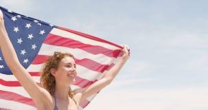 Seitenansicht der kaukasischen Frau mit wellenartig bewegendem Betrieb der amerikanischen Flagge auf dem Strand 4k stock video