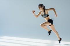 Seitenansicht der laufenden Frau in der sportiven Kleidung Lizenzfreie Stockbilder
