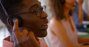 Seitenansicht der männlichen Exekutive des Afroamerikaners, die auf Kopfhörer am Schreibtisch im Büro 4k spricht stock video footage