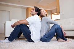 Seitenansicht der Paare, die auf dem Fußboden sitzen Stockbilder