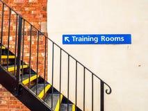 Seitenansicht der schwarzen Metalltreppe mit Richtungszeichen Trainings-Räumen Stockfotos