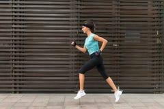 Seitenansicht der sportlichen jungen Frau, die auf einem Bürgersteig läuft lizenzfreie stockbilder
