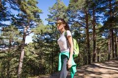Seitenansicht der Wandererfrau gehend auf einen Waldweg Stockfotografie