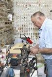 Seitenansicht des älteren Bauschlossers Schlüssel im Speicher machend Stockfoto