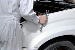 Seitenansicht des Automobilmechanikers in der Uniform mit Schlüssel Maschine unter Haube des Autos an der Reparaturgarage bestimm Lizenzfreies Stockfoto