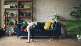Seitenansicht des dünnen Mädchens das Yoga zu Hause tuend, das Sun-Gruß-Surya Namaskara-Komplex auf Boden von schönem übt stock footage
