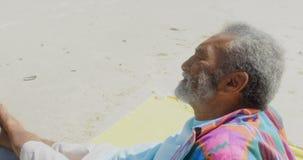 Seitenansicht des durchdachten aktiven älteren Afroamerikanermannes, der auf Strand im Sonnenschein 4k sich entspannt stock video