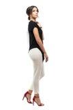Seitenansicht des erfolgreichen jungen Geschäftsfraugehens und der tragenden Anzugsjacke oben schauend Stockbild