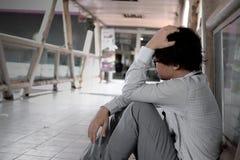 Seitenansicht des frustrierten betonten jungen asiatischen Geschäftsmannes mit den Händen auf Hauptgefühl versuchte oder Sorge Stockbild