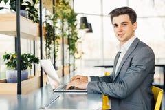 Seitenansicht des Geschäftsmannes sitzend durch die Tabelle mit Laptop-Computer und Kamera betrachtend Lizenzfreie Stockfotos