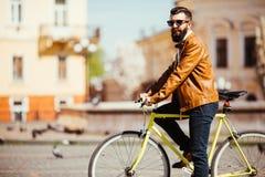 Seitenansicht des hübschen jungen bärtigen Mannes in der Sonnenbrille, die beim auf sein Fahrrad draußen fahren weg schaut Stockbilder