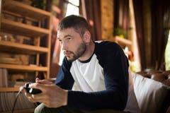 Seitenansicht des hübschen jungen Mannes, der Gamecontroller, Videospiel spielend hält lizenzfreies stockbild