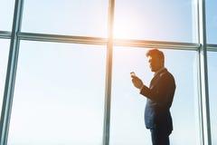 Seitenansicht des jungen Geschäftsmannes steht nahe einem panoramischen Fenster und betrachtet das Telefon Lizenzfreie Stockfotos