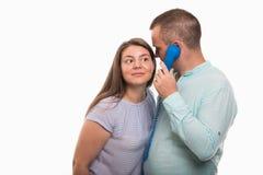 Seitenansicht des jungen glücklichen Paars hörend auf blauem Empfänger Stockfotos