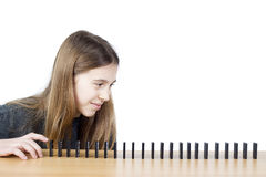 Seitenansicht des jungen Mädchens bereit, den ersten Domino in Folge zu drücken lokalisiert auf weißem Hintergrund Lizenzfreies Stockbild