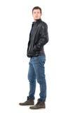 Seitenansicht des jungen Mannes in der Lederjacke und in Jeans, die zurück über der Schulter schauen Lizenzfreie Stockfotos
