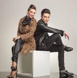 Seitenansicht des jungen Modepaarsitzens Stockbild