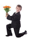 Seitenansicht des kleinen Jungen im Anzug, der Blumen zum someb gibt Stockbild