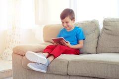 Seitenansicht des kleinen Jungen sitzend auf Sofa mit Tablette Stockfoto