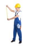 Seitenansicht des Mannerbauers im blauen Overall, der Maßband hält Stockfotografie