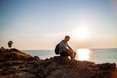 Seitenansicht des Mannes mit dem Rucksack, der Meer beim Sitzen auf H?gel gegen Himmel w?hrend des sonnigen Tages betrachtet lizenzfreie stockbilder