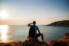 Seitenansicht des Mannes mit dem Rucksack, der Meer beim Sitzen auf H?gel gegen Himmel w?hrend des sonnigen Tages betrachtet stockfotos