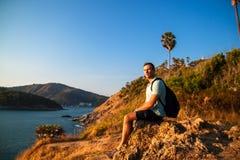 Seitenansicht des Mannes mit dem Rucksack, der Meer beim Sitzen auf H?gel gegen Himmel w?hrend des sonnigen Tages betrachtet lizenzfreie stockfotos