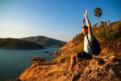 Seitenansicht des Mannes mit dem Rucksack, der Meer beim Sitzen auf H?gel gegen Himmel w?hrend des sonnigen Tages betrachtet stockfoto