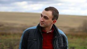 Seitenansicht des Porträts des jungen Lächelns des gut aussehenden Mannes im Freien stock video