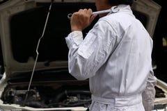 Seitenansicht des professionellen jungen Mechanikermannes im einheitlichen haltenen Schlüssel gegen Auto in der offenen Haube an  Stockfotografie