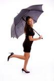 Seitenansicht des reizvollen Frauenholdingregenschirmes Stockbilder