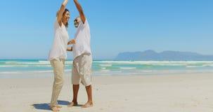 Seitenansicht des romantischen aktiven älteren Afroamerikanerpaartanzens zusammen auf dem Strand 4k stock video footage