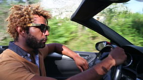 Seitenansicht des schwarzen Mannes konvertierbares Auto durch traditionelle alte Stadt fahrend stock video