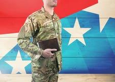 Seitenansicht des Soldaten ein Buch vor amerikanischer Flagge halten Lizenzfreies Stockbild